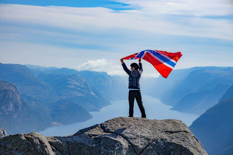 Женщина с размахом флага Норвегии на фоне природы стоковое фото