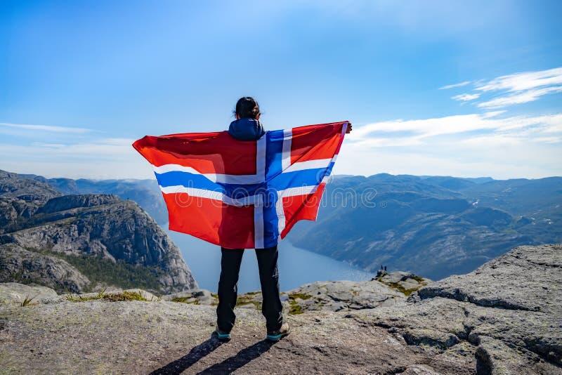 Женщина с размахом флага Норвегии на фоне природы стоковая фотография