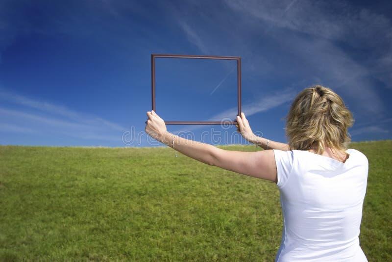 Женщина с рамкой на большом лужке стоковое изображение