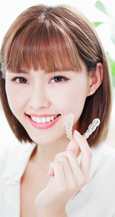 Женщина с расчалкой зубов невидимой стоковое фото rf