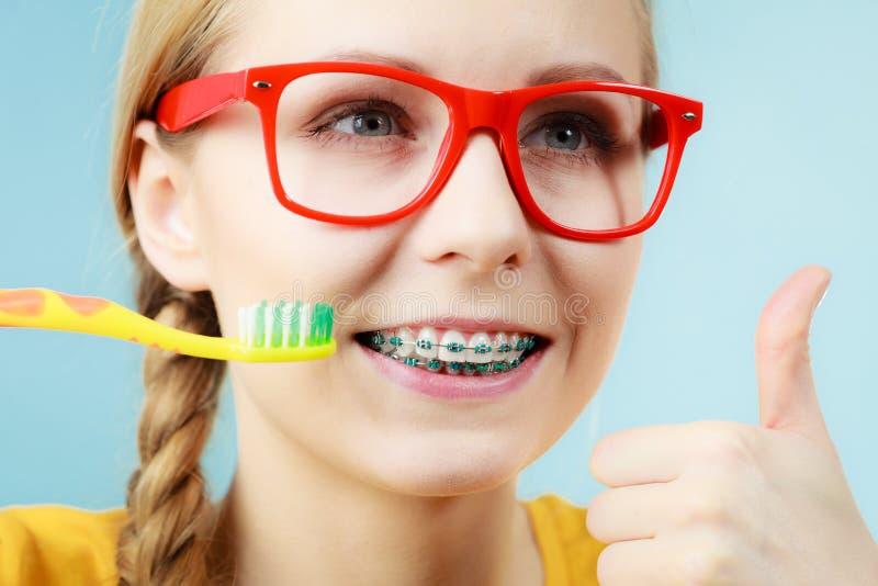 Женщина с расчалками зубов используя щетку стоковая фотография rf