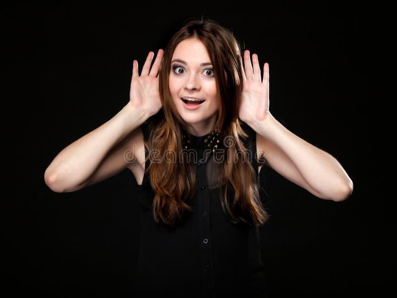 Женщина с руками к уху слушая, сплетня стоковое фото rf