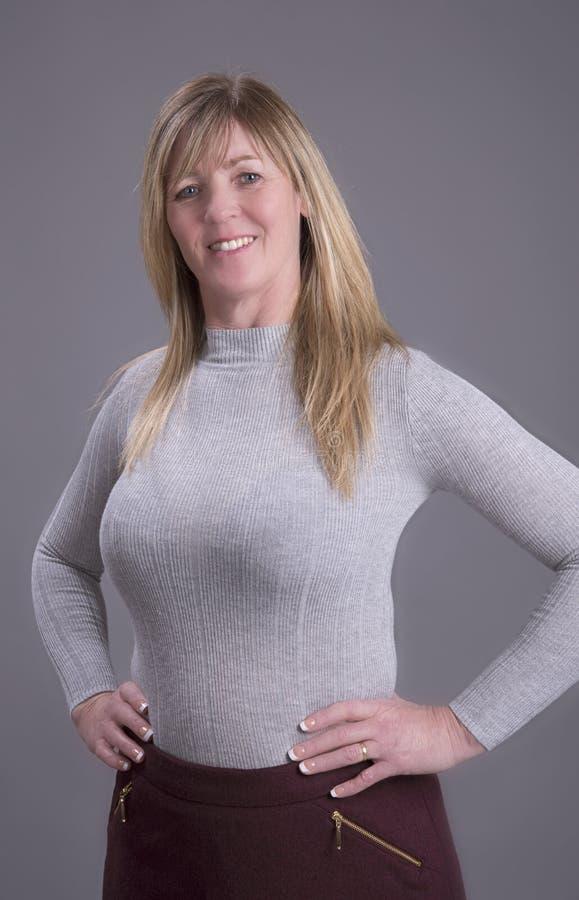 Женщина с руками на талии нося плотный шлямбур стоковое фото