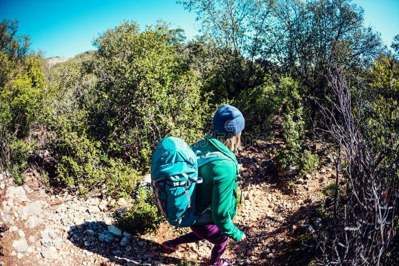 Женщина с рюкзаком в горах стоковые изображения