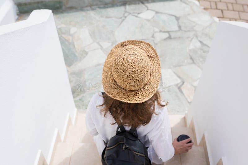 Женщина с рюкзаком в соломенной шляпе и бумажным стаканчиком кофе сидит на шагах и ослабляет курортного города Индивидуальный пут стоковые фото