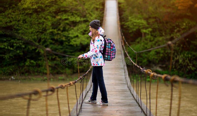 Женщина с рюкзаком, путешествующая по миру, мечтает о новом лесе и пересекает реку в лесном активном отдыхе стоковое фото