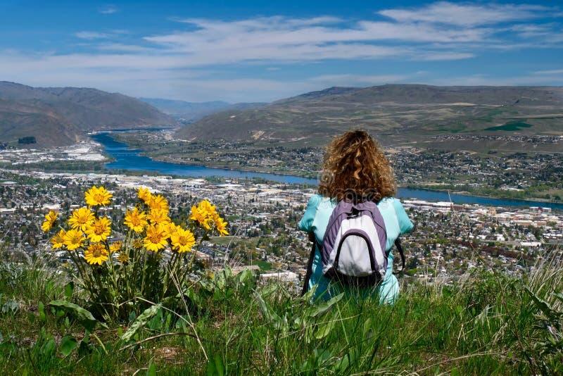 Женщина с рюкзаком сидя на верхней части горы наслаждаясь сценарными взглядами города и реки стоковая фотография