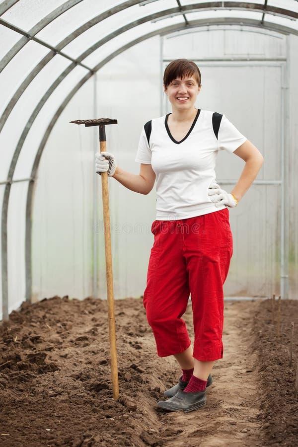 Женщина с сгребалкой в оранжерее стоковое фото rf