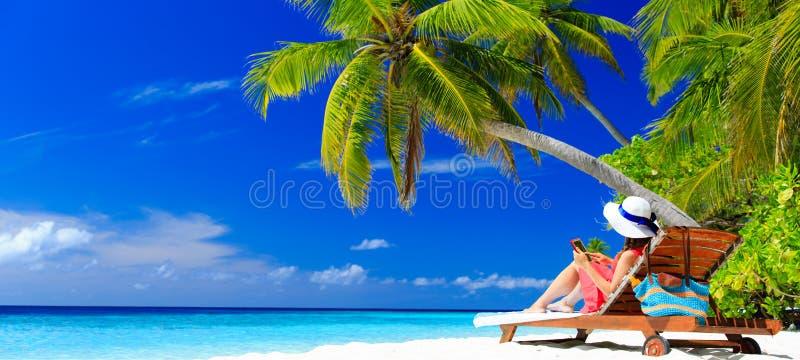 Женщина с сенсорной панелью на тропическом пляже стоковое фото