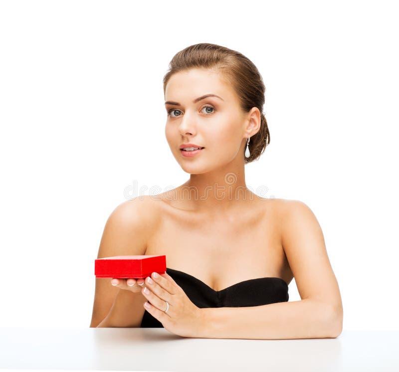 Женщина с серьгами и подарочной коробкой диаманта стоковое изображение rf