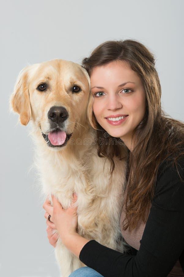 Женщина с собакой золотого retriever на белой предпосылке стоковая фотография rf