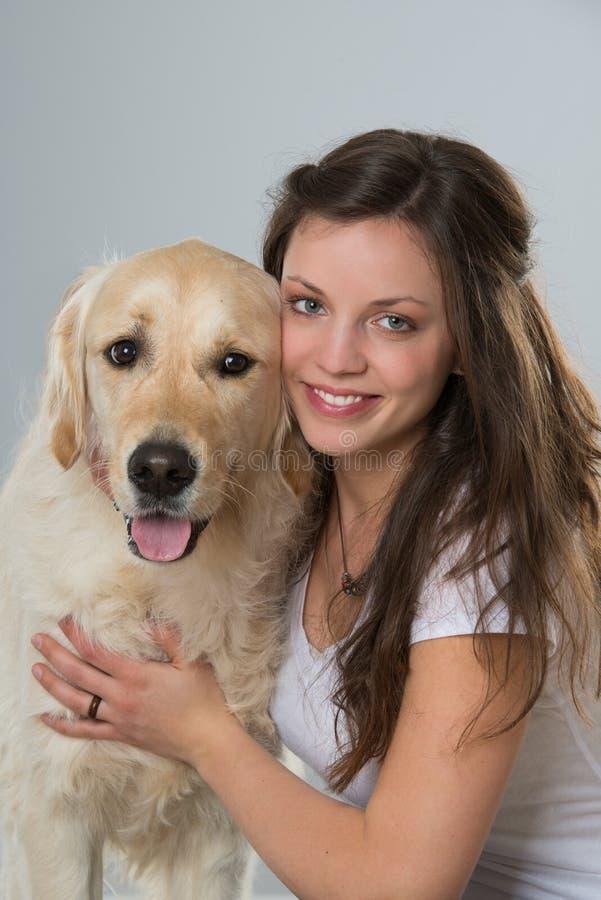 Женщина с собакой золотого retriever на белой предпосылке стоковая фотография