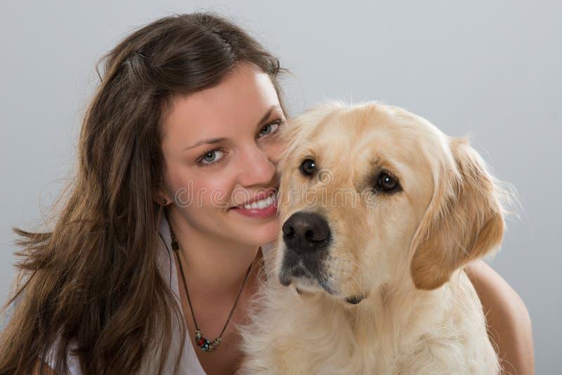 Женщина с собакой золотого retriever на белой предпосылке стоковые фотографии rf