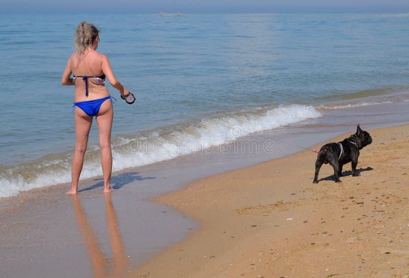 Женщина с собакой на пляже морем стоковая фотография