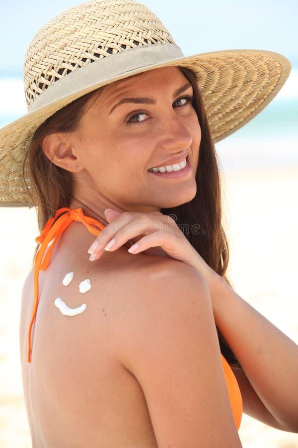 Женщина с солнцезащитным кремом стоковое фото rf