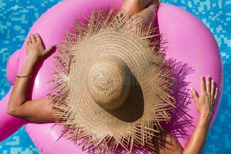 Женщина с соломенной шляпой в бассейне с раздувной розовой игрушкой стоковые изображения