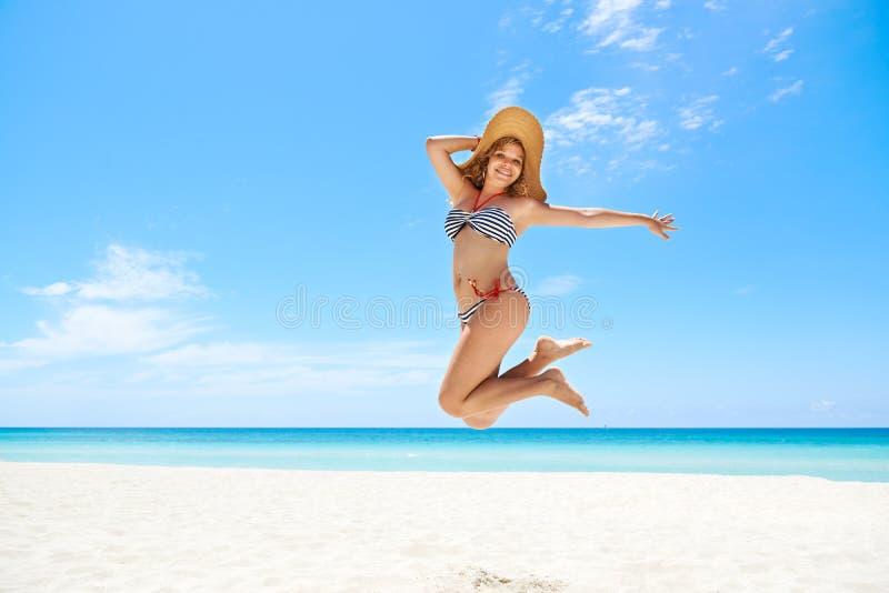 Женщина с средний-воздухом соломенной шляпы скача на пляже стоковое фото