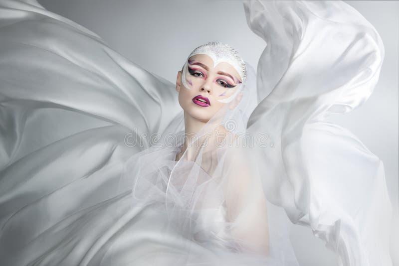 Женщина с творческим составом в белом летании ткани Девушка держа ткань белизны летания стоковое фото rf