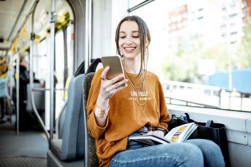 Женщина с телефоном в общественном транспорте стоковые фото