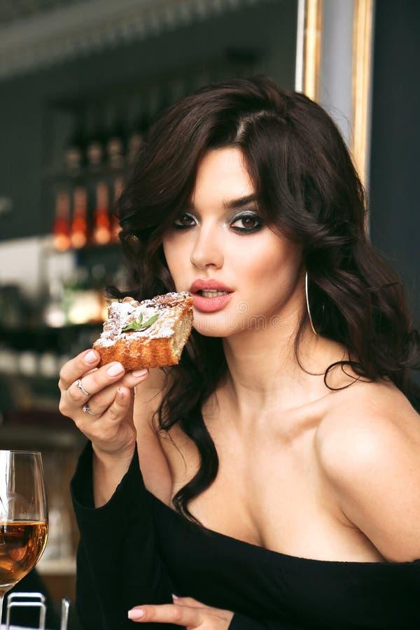 Женщина с темным вьющиеся волосы в элегантном платье сидя в элегантном r стоковое фото