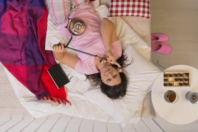 Женщина с телефоном в кровати стоковое фото