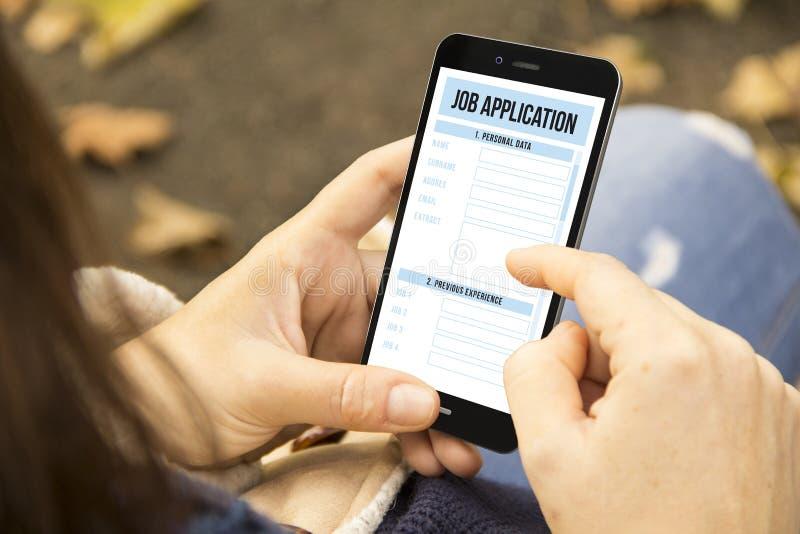 Женщина с телефоном заявления о приеме на работу в парке стоковая фотография