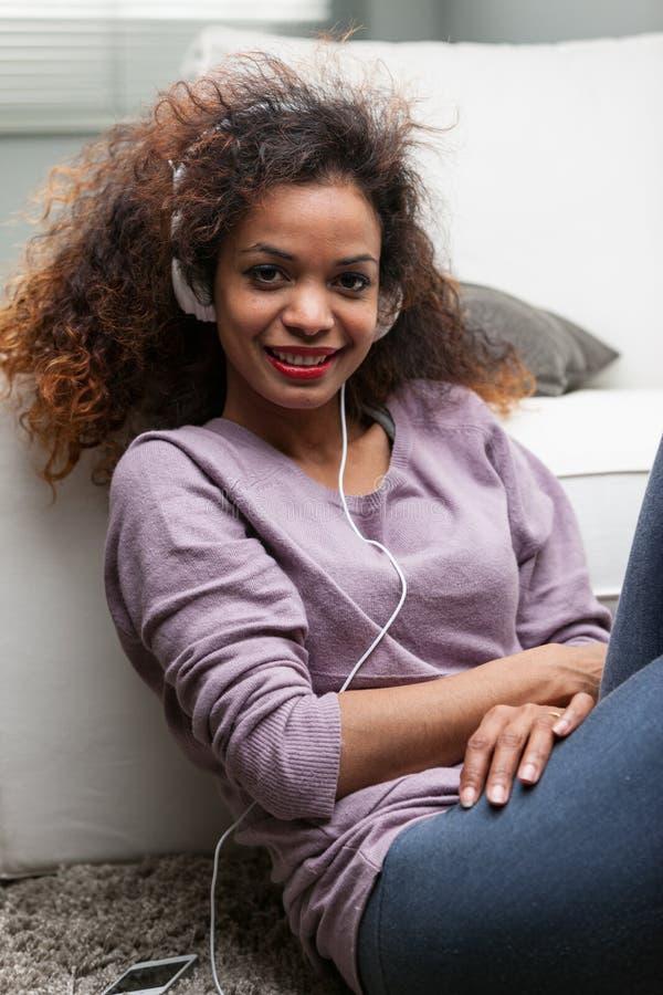 Женщина слушая к музыке в ее прожитии стоковая фотография