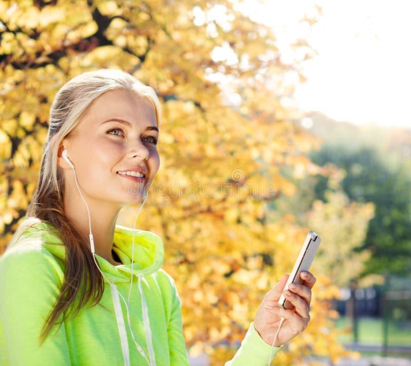 Женщина слушая к музыке outdoors стоковая фотография