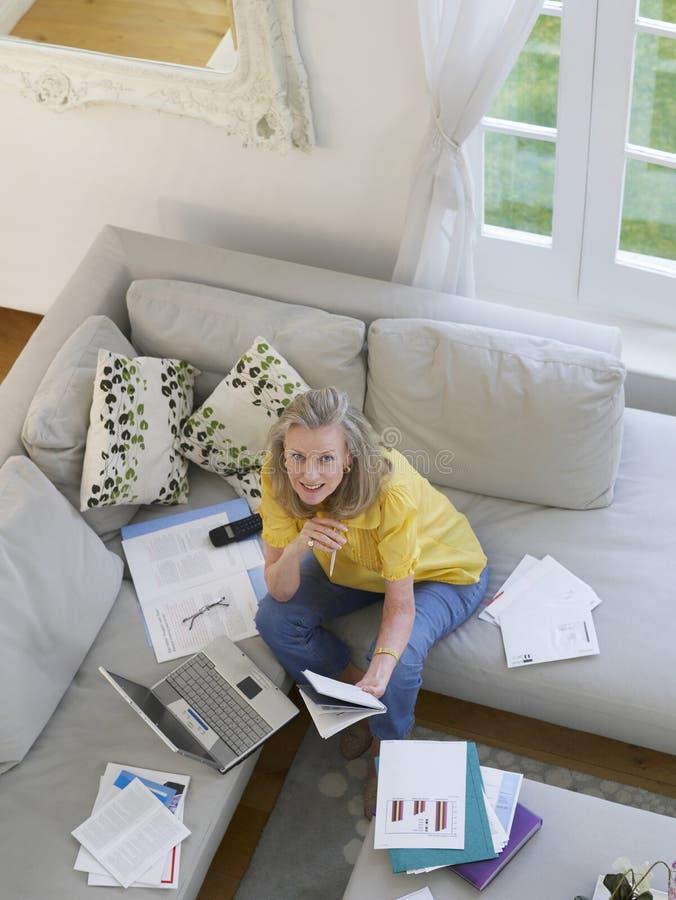 Женщина с финансовыми документами и компьтер-книжкой стоковое изображение