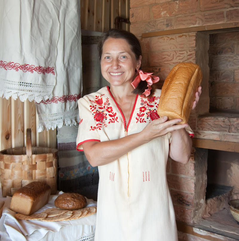 Женщина с хлебом около традиционной русской печки стоковая фотография