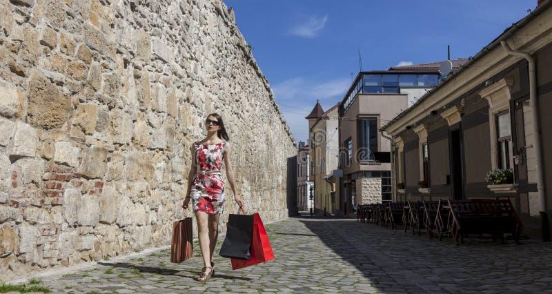 Женщина с хозяйственными сумками в городе стоковая фотография