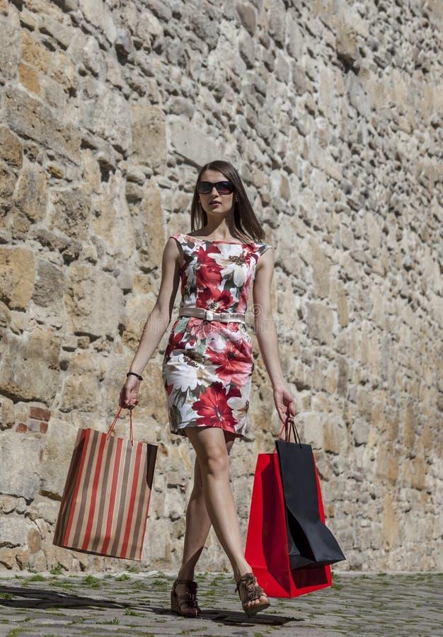 Женщина с хозяйственными сумками в городе стоковые фото