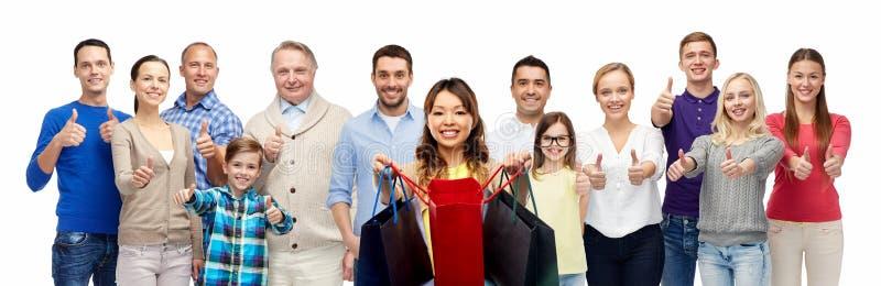 Женщина с хозяйственными сумками и люди показывают большие пальцы руки вверх стоковые фотографии rf