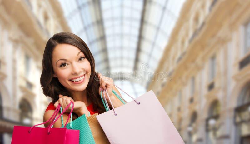 Женщина с хозяйственными сумками над предпосылкой торгового центра стоковая фотография rf