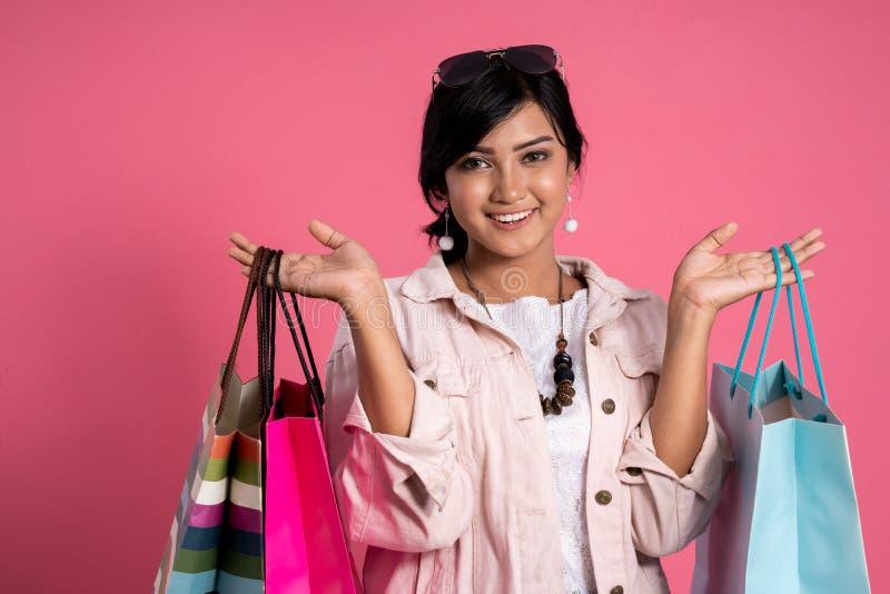 Женщина с хозяйственными сумками над розовой предпосылкой стоковое изображение