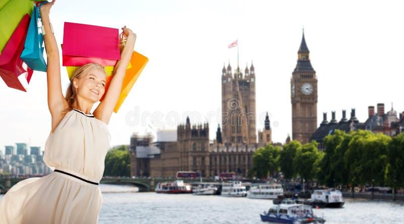 Женщина с хозяйственными сумками над городом Лондона стоковые изображения rf