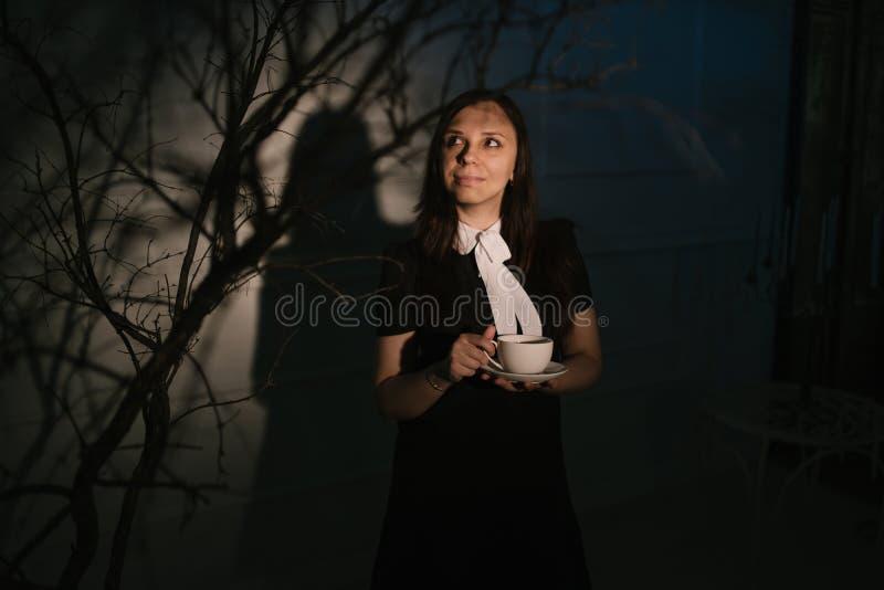 Женщина с чашкой кофе в темном месте стоковое изображение