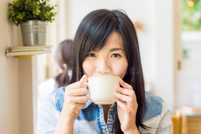 Женщина с чашкой кофе усмехаясь в кафе стоковые изображения