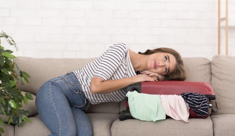 Каникулы мечты Женщина с чемоданом сидя на софе стоковые изображения
