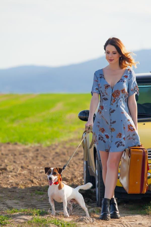 Женщина с чемоданом и собакой около автомобиля стоковая фотография rf