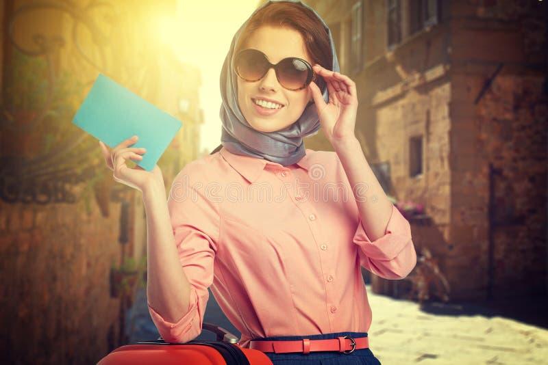Женщина с чемоданом на улице стоковое фото
