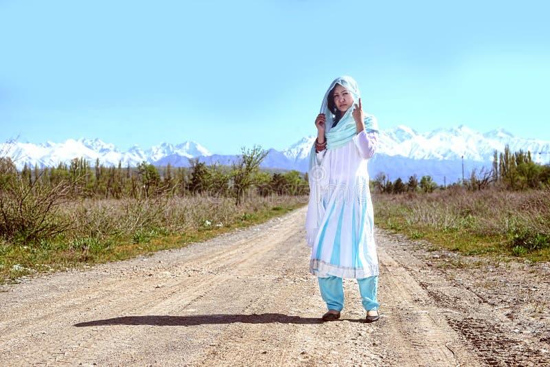 Женщина с черными волосами в голубом сари, на rular дороге, природа стоковые фотографии rf