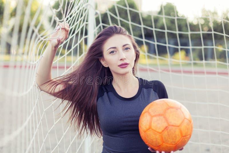 Женщина с шариком в угле цели футбола стоковое фото rf