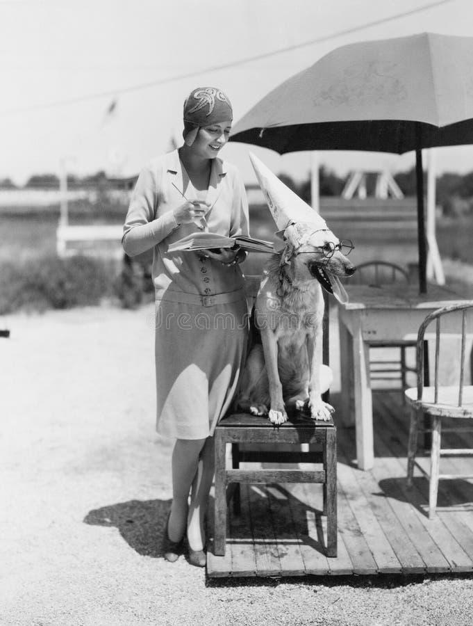 Женщина с шляпой и стеклами собаки нося стоковое фото