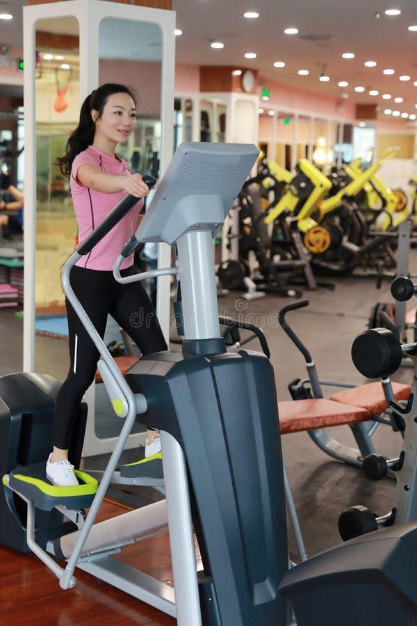 Женщина с эллиптическим перекрестным тренером на спортзале Мышечный, внутренний стоковая фотография
