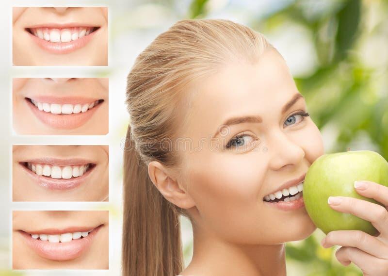 Женщина с яблоком и улыбками стоковые изображения rf