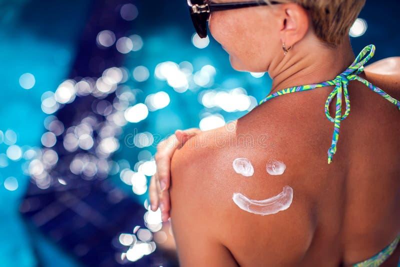 Женщина с crem солнца на ей назад в форме улыбки Люди, лето, каникулы и концепция здравоохранения стоковое изображение