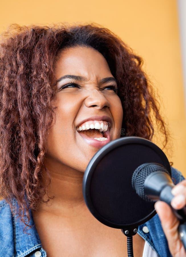 Женщина с Frizzy волосами поя пока смотрящ прочь стоковая фотография rf