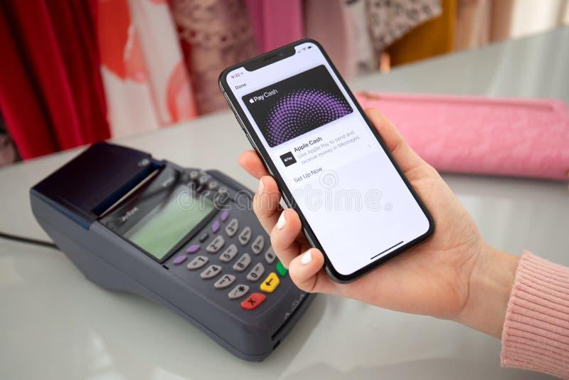 Женщина с iPhone с Apple Pay Cash и терминалом в сети стоковая фотография rf