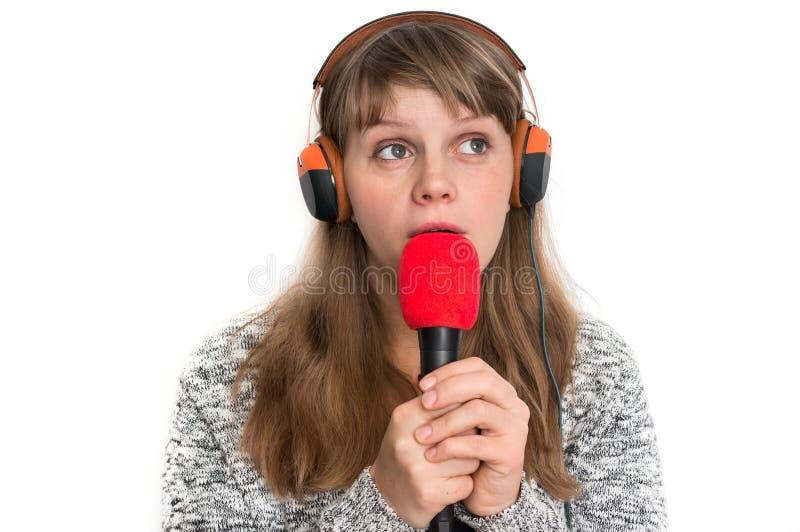 Женщина с mic и наушниками записывает ее песню стоковое фото rf